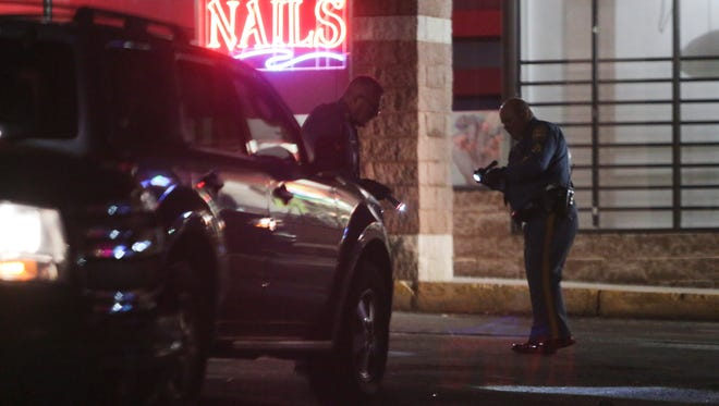 Delaware State Police officers investigate in the Canby Park Shopping Center parking lot after a person was shot there shortly after 9 p.m. Friday.