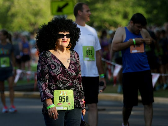 Arletta Miller wears an afro wig during the second annual High Street Hustle 8K, 5K, and 1K in downtown Salem on Saturday, Aug. 13, 2016.