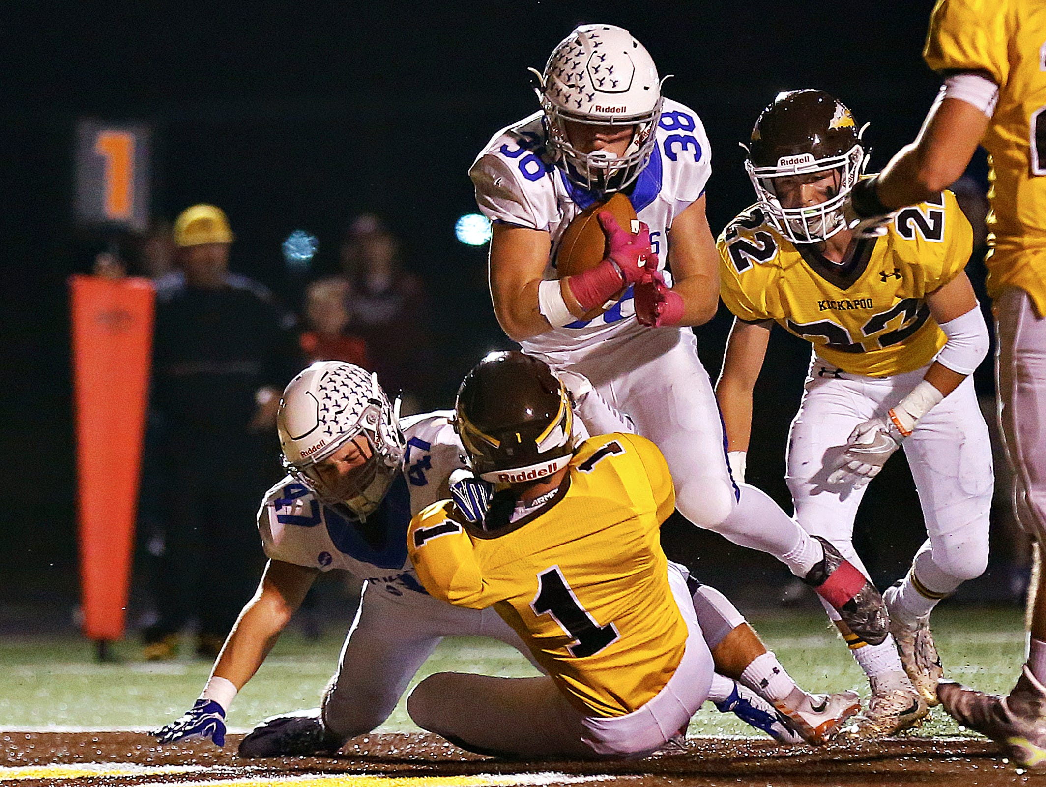 Rockhurst High School running back Brady McCanles (38) barrels over Chiefs cornerback Peyton Moore (1) to score a touchdown during first quarter action of the Class 6 playoff game between Rockhurst High School and Kickapoo High School played at Pottenger Stadium in Springfield, Mo. on Oct. 28, 2016.