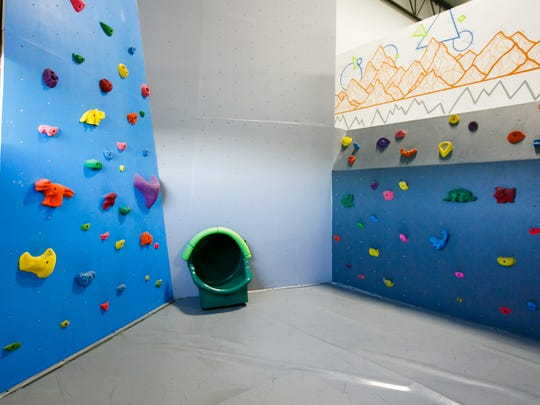 The kids area at climbing gym Rock Boxx has large climbing holds shaped like various animals and dinosaurs and a tube slide for those able to get over the ledge.