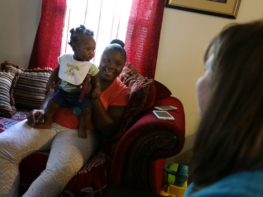 Brittany Addison, 22, holds her son Kaiden Cotton, 7-months-old, while talking with nurse Jennifer Turner during a home visit from the Nurse- Family Partnership in Darlington, SC in June 2016.