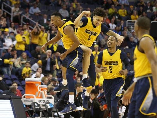 Michigan Wolverines guard Zak Irvin (21) and Wolverines forward D.J. Wilson (5) celebrate in the first half against the Illinois Fighting Illini during the Big Ten Conference Tournament at Verizon Center.
