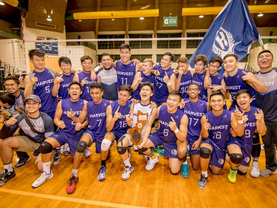 Harvest Christian Academy players gather for a photograph with supporters after beating the Tiyan High School at the IIAAG Volleyball championship game.