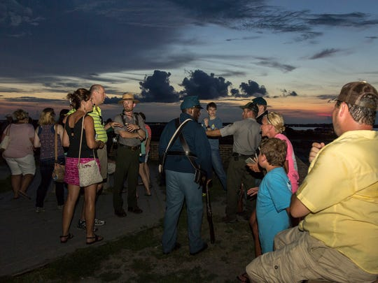 Tour guides, including National Park Service rangers and representatives from the Youth Conservation Corps,  lead the Candlelight Program through Fort Pickens on July 22, 2016.