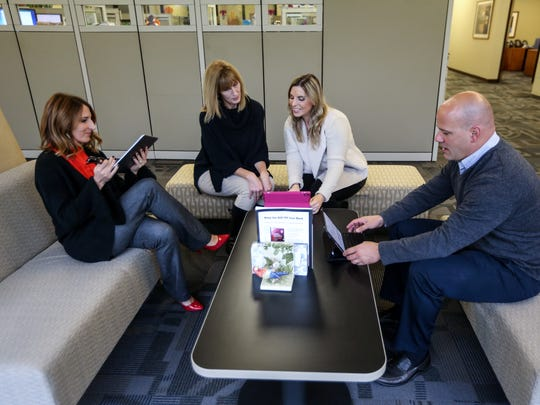 From left, Sara Armstrong, wellness manager; Christina Ozee, reporting analyst; Jennifer Malinowski Teague, corporate wellness coordinator, and Brad Labadie, client executive, work on the iPads the company bought all employees for meeting a corporate goal a year ahead of schedule at the Kapnick Insurance Group office.