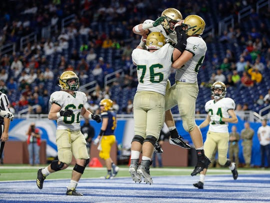 Jackson Lumen Christian players celebrate scoring a 2-point conversion during the second half of Lumen Christi's 40-34 win over Ithaca in the Division 6 state title game on Friday, Nov. 24, 2017, at Ford Field.
