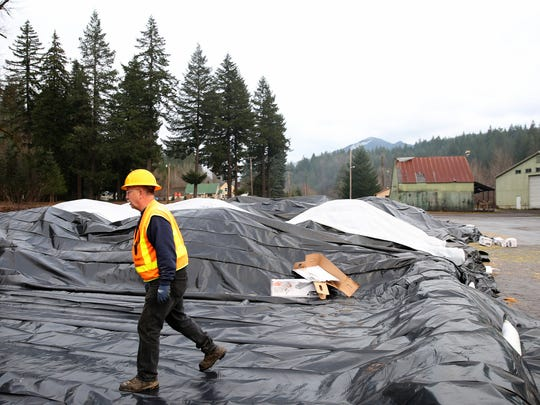 Alan Dimock, a hazmat technician with NWFF Environmental, lays out tarp for contaminated soil to be dropped off near the site of a fuel tanker truck crash on Highway 22 at milepost 63 on Monday, Dec. 18, 2017. Highway 22 remains closed from east of Detroit to Highway 20 near the Santiam Pass.