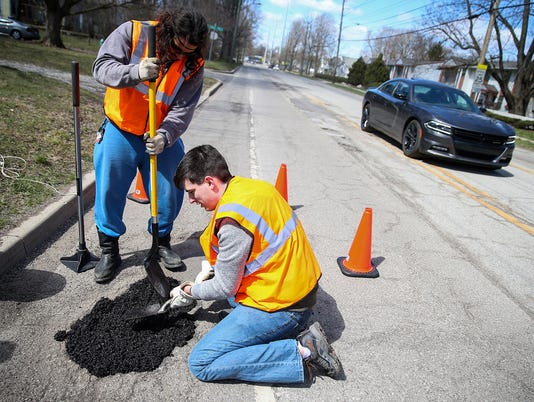 636587158085242777-2-guys-fill-potholes-on-their-own-JRW01.JPG
