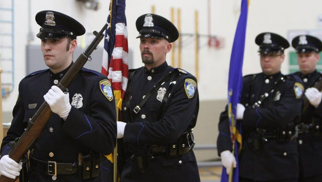 The Menomonee Falls Police Department Honor Guard presents the colors during the annual Veterans Day ceremony in 2014. The village plans to add three full-time police officers and six full-time firefighters to its ranks in 2018.