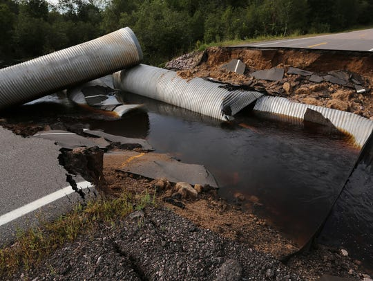 Culverts and pieces of asphalt are strewn about after