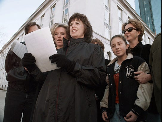 Carol Hacker (center) and other supporters for the victims of the Oklahoma City bombing sing Christmas carols across the street from the federal courthouse in Denver on Dec. 23, 1997, where a jury convicted Oklahoma City bombing defendant Terry Nichols of involuntary manslaughter and conspiracy.