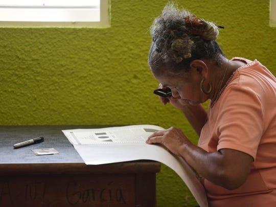 Puerto Rican resident Maria Quinones looks carefully
