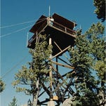 Cathy Hutchinson stands on the catwalk of the West White Pine Mountain fire lookout in 1965.