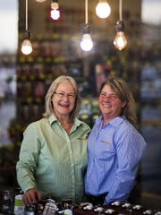 Jane Watts, left, stands with her partner, June Riner, at one of the battery and light bulb stores they co-own in Decatur, Ga.