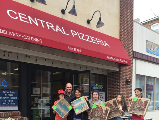 Students show off their pizza boxes marked for the