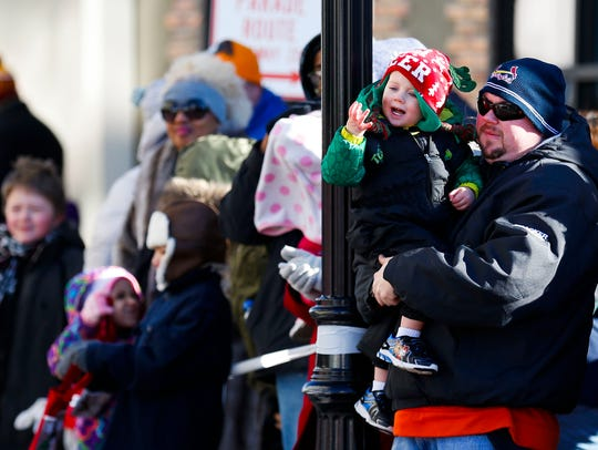Two-year-old Miles Simpson waves at a float as his uncle Jeffery Simpson holds him up during the 2017 Downtown Springfield Christmas Parade in downtown Springfield on Dec. 9, 2017.