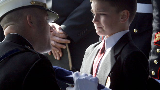 Lt. Col. Ric Thompson hands 8-year-old Christian Golczynski the flag off the coffin is his father, Marine Staff Sgt. Marcus Golczynski, who was killed in Iraq. The iconic image of a young boy's courage is inspiration for A Soldier's Child Foundation, which provides birthday gifts to children of fallen soldiers.