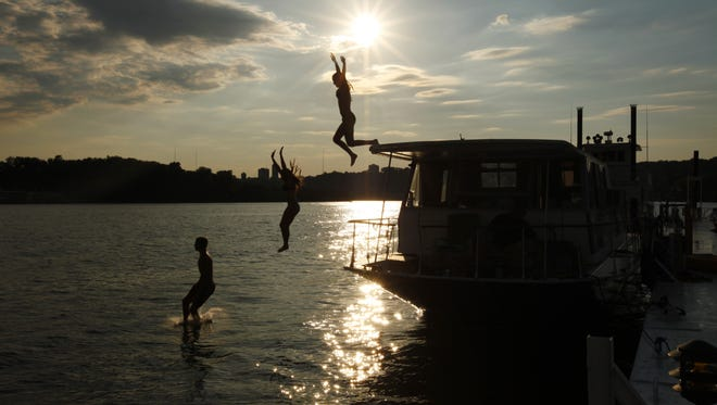 Caelan Hueber, 17, of East Walnut Hills, Katie Ryan, 16, of Anderson, and Bryce Hueber, 16, of East Walnut Hills, jump into the Ohio River from the Huebers' dad's houseboat, docked at the Ohio River Launch Club in the East End. During the summer, the Hueber kids are at the boat several times a week.