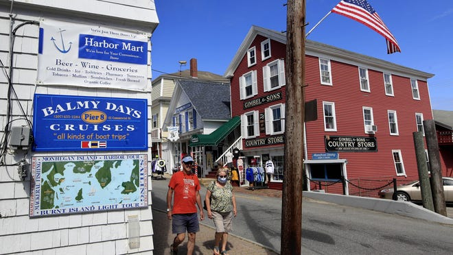 Visitors walk June 9, 2020, through the shopping district in Boothbay Harbor, Maine.
