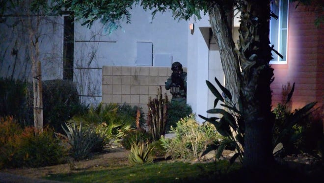 Desert Regional SWAT team member moves into position at a home on Skylar Lane in the Escena community in Palm Springs on Friday, Feb. 5, 2015.