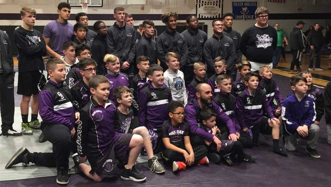 The Old Bridge High School wrestling team poses for a group photo with some of the township's youth grapplers following Friday night's upset of Piscataway.