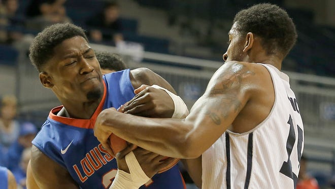Louisiana Tech's Merrill Holden (21) fights for the ball with Rice guard Bishop Mency (15) in a game earlier this month.