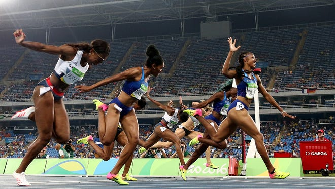Brianna Rollins leads an American sweep in the 100 hurdles, leaving Great Britain's Cindy Ofili, left, in fourth. Ofili if from Ypsilanti.