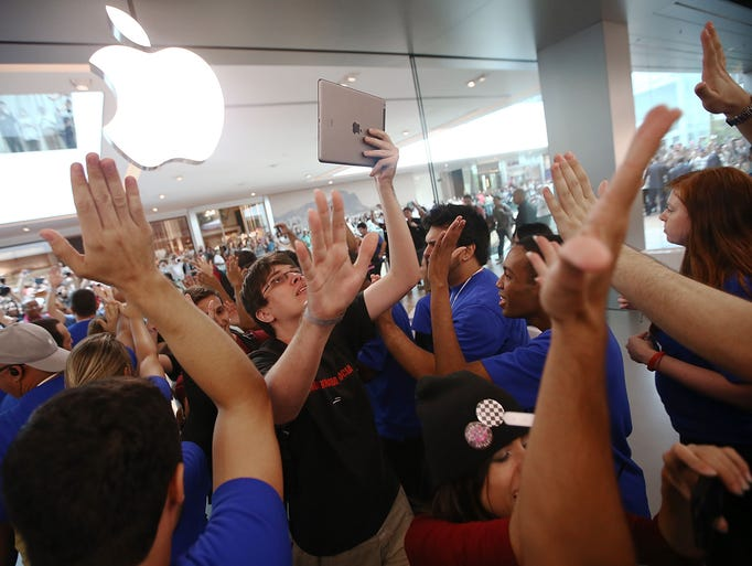 A customer  celebrates after entering Brazil's first Apple retail store minutes after it opened in the Village Mall shopping center in Rio de Janeiro.