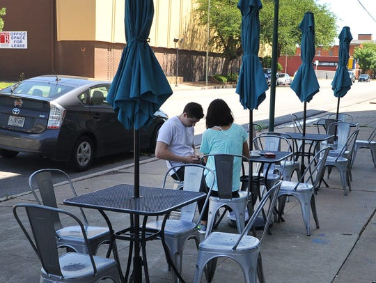 A young couple shares a table outside of the Odd Duck