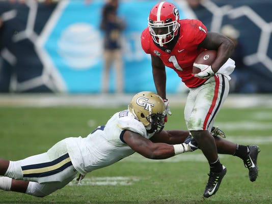 Georgia running back Sony Michel (1) runs by Georgia Tech linebacker Victor Alexander (9) during the second half of an NCAA college football game, Saturday, Nov. 25, 2017, in Atlanta. Georgia won 38-7. (AP Photo/John Bazemore)