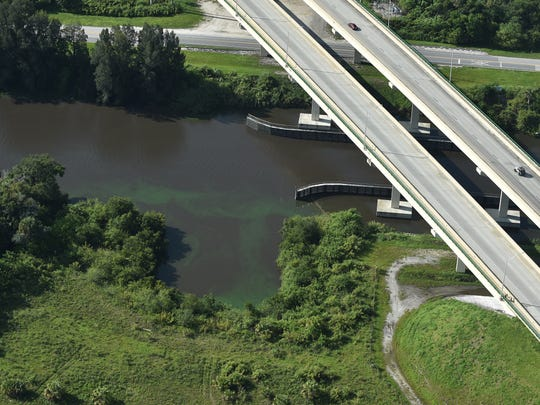 Algae can be seen in the C-44 Canal at the Warfield Boulevard Bridge at Indiantown on Friday, June 8, 2018.