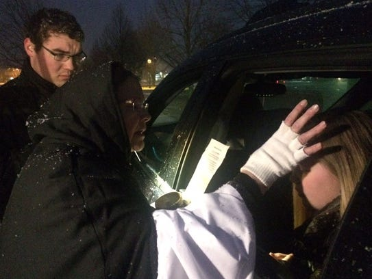 As snow falls, Deacon Mary Lynn Adams applies ashes