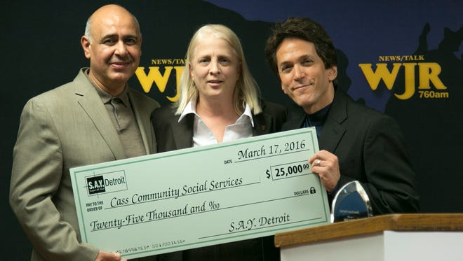Mitch Albom, right, and Dr. Chad Audi, president of the Detroit Rescue Mission Ministries, present a $25,000 check to Faith Fowler, executive director of Cass Community Social Services, from a donation raised through the S.A.Y. Detroit Radiothon in December. Cass Community Social Services serves thousands of meals every year, offers job training for at-risk citizens and jobs to those who face barriers to unemployment.