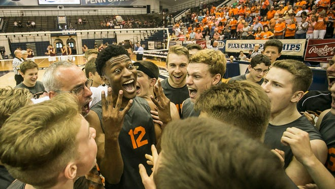 Northeastern's Jeff Reynolds, middle, celebrates the Bobcats' fourth straight PIAA Class AA state title with his teammates on Saturday.