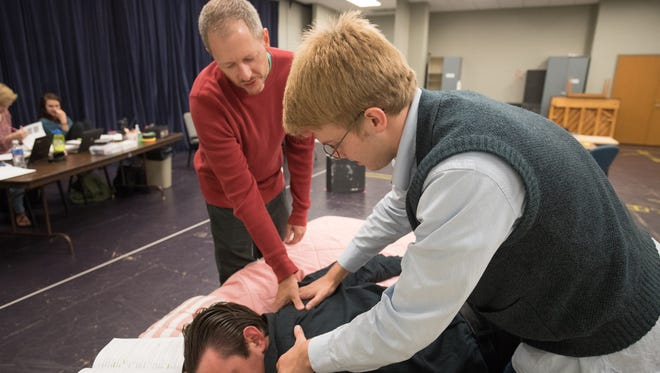 "Director Tyler Marchant works with theatre arts students B.J. Sudhoff and Alex Friedemann (face down) as they rehearse ""Unnecessary Farce,"" which will be performed at the University of Wisconsin–Stevens Point Oct. 14-15 and 19-22."