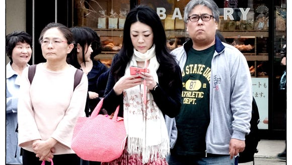 A woman checks her smartphone while walking down the