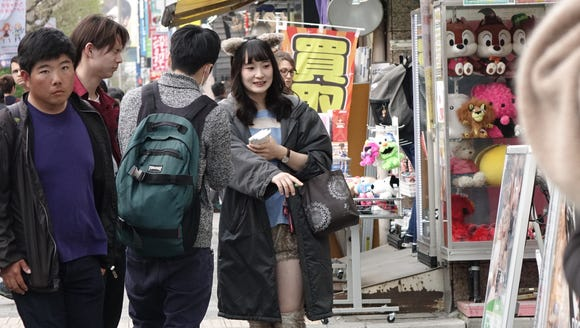 A woman hands out flyers for a Maid Cafe in Tokyo