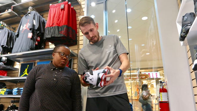 Hibbett Sports team manager Andy Lewis, right, looks over Nike Air Jordan shoes with assistant manager Tenika Stroble, left, in the store at the Anderson Mall on Thursday. The store opens Saturday morning.