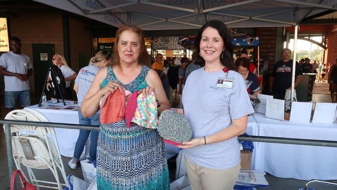 "At the game, I gave 50 hats to Diedre Blaus, right, administrative director of the Steeplechase Cancer Center. She said our creations were ""beautiful."""