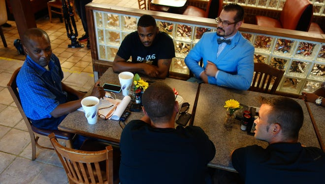 Actiivist Jack Logan (far left) meets with Andre Gregory of Black Lives Matter and Daniel Sheppard of FOAK Thursday night.