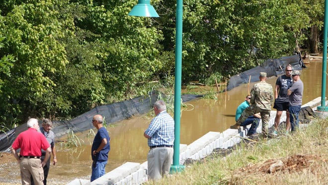 Ermergencency Management Director Jerry Buchanan, second from left, talks with others as the search commences for a man missing in the Red River.