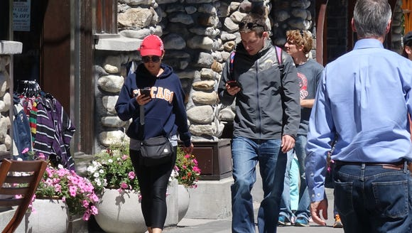 A couple walks down the street in Banff, Alberta looking