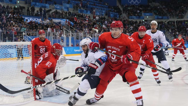 Feb 17, 2018; Gangneung, South Korea; United States forward Brian Gionta (12) battles for the puck into the boards with Russia defenseman Bogdan Kiselevich (55) in the third period during men's ice hockey Group B play in the Pyeongchang 2018 Olympic Winter Games at Gangneung Hockey Centre.