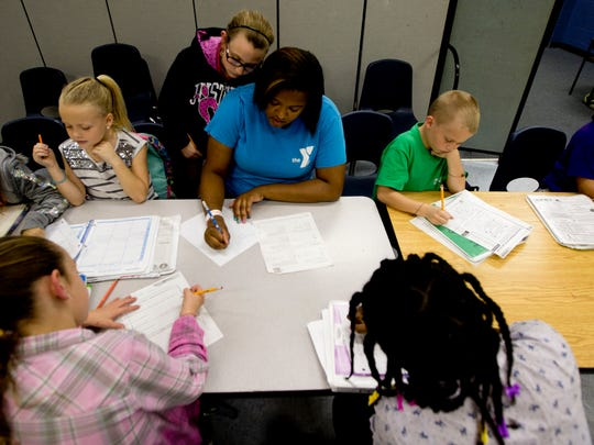 "Marshay Gates, an after school counselor with the Lee County YMCA helps public school students with their homework on Wednesday 1/7/2014. Currently, public school students are not legally allowed to ""opt-out"" of tests. The group's bill would seek to change that."