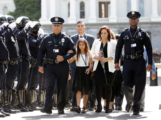 Susana Vega, the wife of Palm Springs Police Officer Jose Gilbert Vega, and their daughter, Vanessa, 9, walked to the Peace Officers Memorial Ceremony, Monday, May 8, 2017, in Sacramento, Calif. Officer Vega, who was among one of the 10 officers, who lost their lives in the line of duty in 2016, were honored during the ceremony. Vega and Palm Springs Police Officer Lesley Zerebny, who was also honored, were shot and killed Oct. 8, 2016 while responding to a domestic dispute.