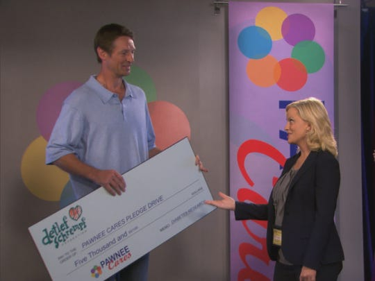 Detlef Schrempf provides a check during Leslie Knope's telethon.