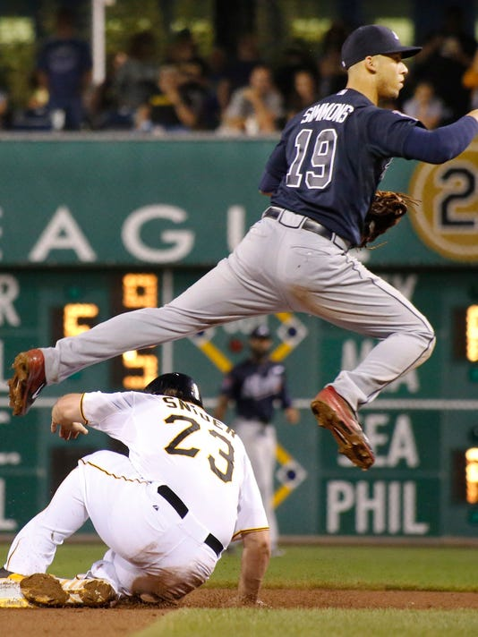 Atlanta Braves shortstop Andrelton Simmons hops over Pittsburgh Pirates' Travis Snider to complete a double play on Chris Stewart in the fifth inning of the baseball game on Wednesday, Aug. 20, 2014, in Pittsburgh. (AP Photo/Keith Srakocic)