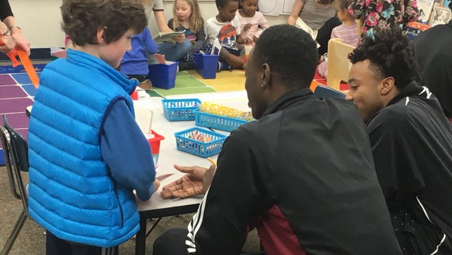 Asheville High basketball players Dontae Burnett and Dalvin Battle have taken part in a elementary-school initiative for the Cougars this week.