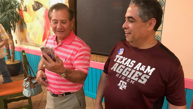 Billy Enriquez, left, and Samuel Garcia get the news via phone call that they both won election to the Abilene Independent School District board of trustees Saturday.