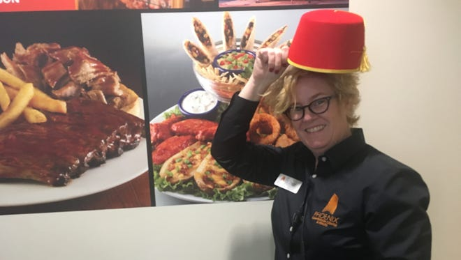 Janay Church, guest experience manager for the Phoenix Convention Center, tries on a hat from the lost and found at Phoenix Comic Fest on May 27, 2018.